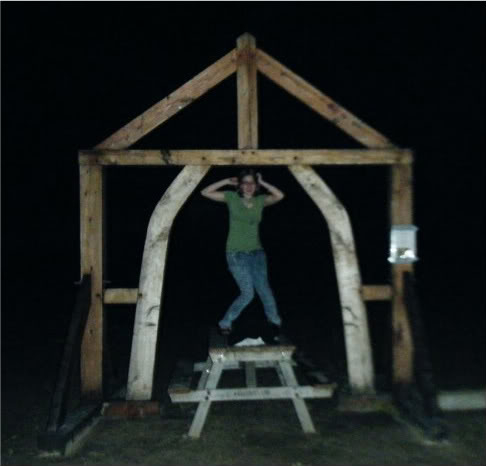 Holly on a picnic table under a post-and-beam arch at night