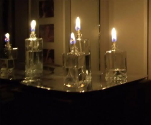five glass oil lamps, lit, in a dark room
