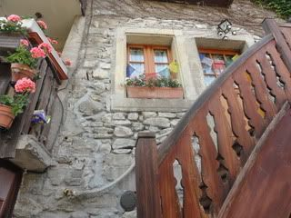 stone building with window boxes, and steep wooden staircase to a second-floor window, in a French town on Lake Geneva