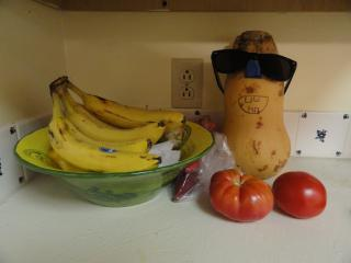 food on a counter; a squash is wearihg sunglasses