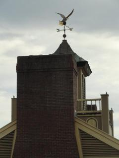 19th century house with a bir landing on a weathervane
