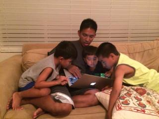 a dad and three kids, reading something on a laptop