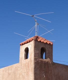 TV antennas on top of a little tile-roofed bell tower, on an adobe building