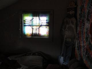 light coming through a painted, tie-dyed cloth over a window, in a dark room