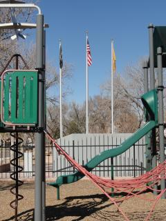 playground equipment with flags and a monument behind