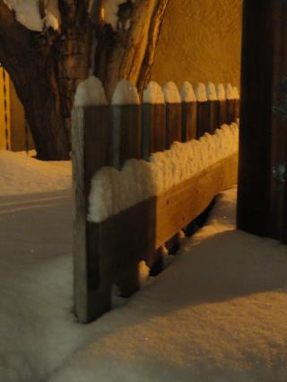 snow, on a wooden fence, in the dark, with shadows