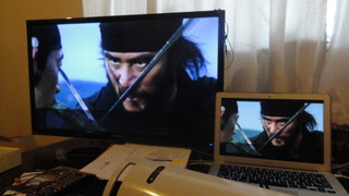 Korean drama action scene with swords, on a desktop, next to a laptop, same image