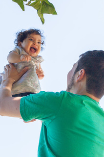 dad lifting a laughing baby