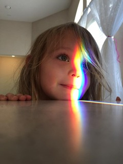 girl with a rainbow on her face from the window