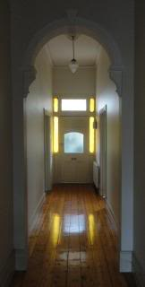 long hallway, tall ceiling, sculpted archway, sun through colored glass reflecting on polished wood floor