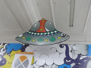 UFO and sky fantasy art up high on the wall and ceiling at a thrift store