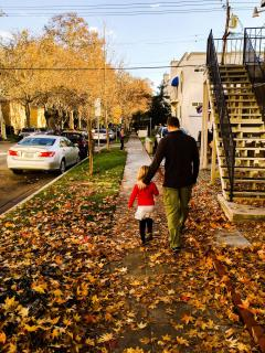 dad and daughter walking on fallen leaves on sidewalk