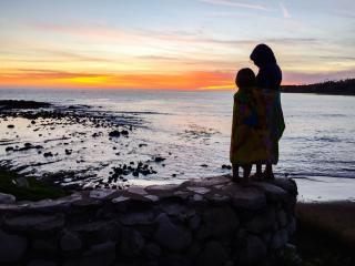 siblings in profile at seaside at sunset