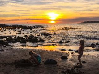two girls on a rockybeach, rocks in the water, cloudy sunset
