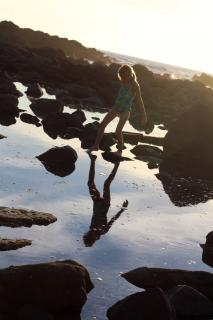 child playing on rocks in a tidepool, with her reflection on the water