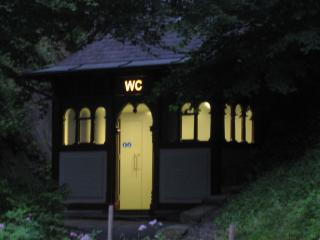 public toilet cottage lit from within at night