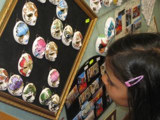girl looking at a display of small ceramic masks