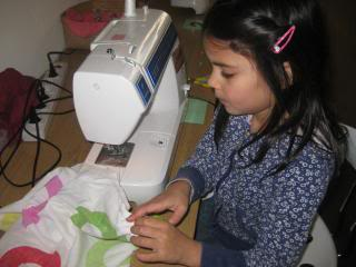 child sewing with sewing machine
