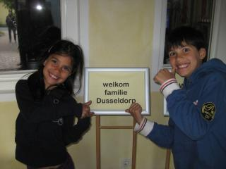 two kids pointing at a sign welcoming their family