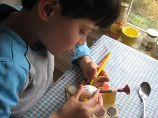 child decorating an egg