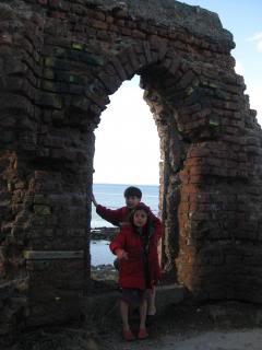 children in arch of ruin near sea