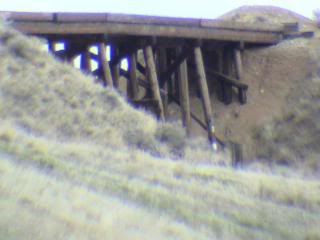 old trestle or bridge made with wooden poles and beams, between two sand hills