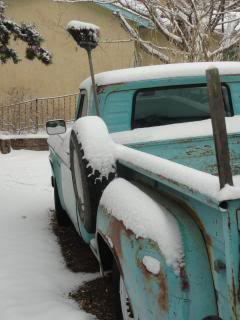 old turquoise pickup truck with snow on it