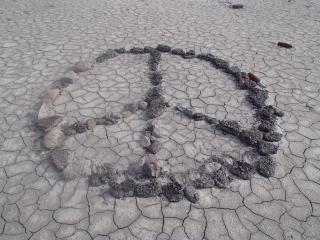 peace symbol made of rocks on dry cracked flat desert