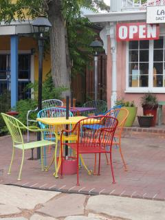 colored metal chairs at an outdoor cafe; sign says OPEN