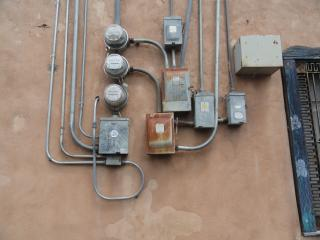 six breaker boxes and three electrical meters, jumbly, on a stucco wall