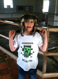 boy with Roman helmet on, and Minecraft t-shirt, at museum