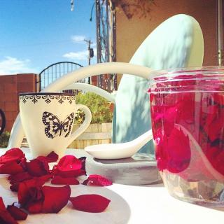 rose petals in a jar, and some scattered on the table, near a teacup
