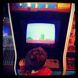 young child playing full-size arcade Super Mario Brothers