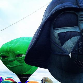 hot air balloons, two nearest are shaped like the heads of Yoda and Darth Vader