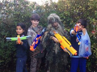 four kids in costume with Nerf guns