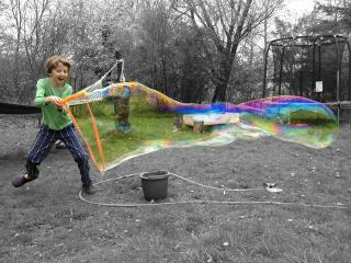 boy making a giant bubble with a stick and cord