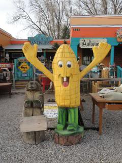 large carved wooden corn-on-thecob-person with arms wide