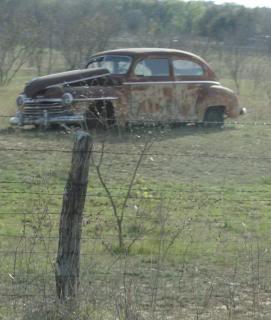 old rusty sedan in a field in Texas
