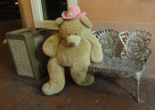 giant teddy bear with pink cowboy hat on a park bench
