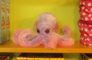 pink and lilac stuffed octopus on a shelf in a toy store
