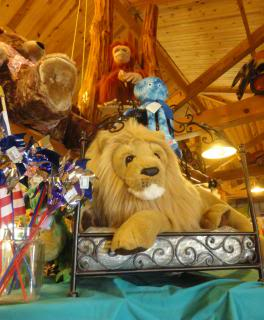 stuffed monkey, stuffed lion, other toys in a museum/store