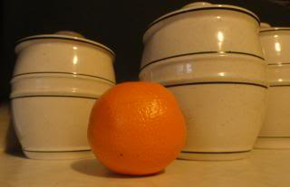 an orange in front of ceramic canisters