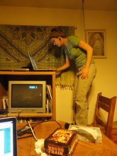 Holly, teen, standing on a chair, using her laptop on top of a TV cabinet