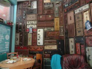 wall made of suitcases and trunks, stacked up, in a cafe in Chichester