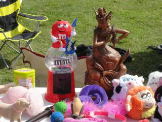 statue, toys, M&M dispenser at a car boot sale display