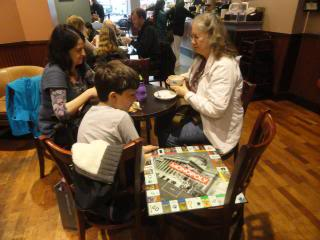 Julie and Adam Daniel, with Joyce Fetteroll at a coffeeshop, with a boardgame on the side