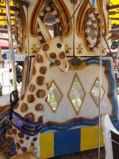 Giraffe to ride, on an outdoor carousel