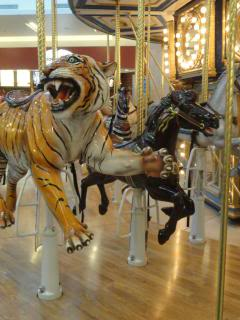 indoor carousel with tiger and black horse