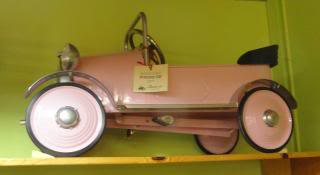 antique pedal car on display in a toy store