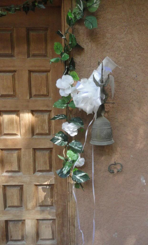 wall-mounted brass bell by a wooden door, decorated with flowers